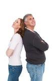 Tillfälliga par som ler och ser upp Arkivfoto