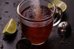 Tillfoga något socker in i ett te Royaltyfria Bilder