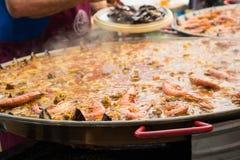 Tillfoga räka och skaldjur till en jätte- paella under matlagning arkivfoton