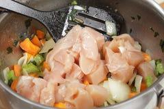 Tillfoga rå hönakuber till risotto royaltyfria foton