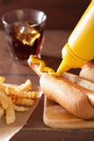 Tillfoga senap till den grillade varmkorven Royaltyfria Foton