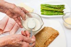 Tillfoga vit sås till quinoakräpparna Royaltyfri Foto