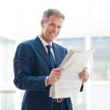 tillfredsställd affärsmantidning som läs royaltyfria bilder