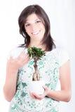 Tillfredsställd brunettkvinna med bonsai Royaltyfri Bild