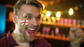 Tillfredsställd engelsk fotbollslagsupporter med flaggan som målas på att hurra för kind lager videofilmer
