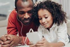 Tillfredsställd farsa och barn som tycker om melodi med hörlurar Fotografering för Bildbyråer