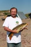 Tillfredsställd fiskare med en stor karp Sötvattens- hav Royaltyfri Bild