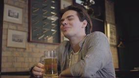 Tillfredsställd grabb som dricker öl som sitter på en tabell i en bar Fritid efter hårt arbete stock video