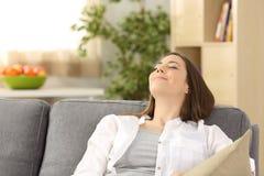 Tillfredsställd kvinna som kopplar av att ligga på en soffa hemma royaltyfri fotografi