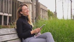 Tillfredsställd kvinnlig student som lyssnar till musik vid vit i öratelefoner och minnestavla på bänk i ultrarapid stock video