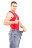Tillfredsställd man för viktförlust i ett par av gammal jeans som ger en tumme Royaltyfri Fotografi