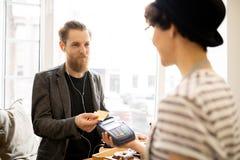 Tillfredsställd man som betalar för räkning i kafé arkivfoto