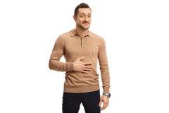 Tillfredsställd man som rymmer hans hand på hans mage arkivfoto