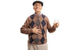 Tillfredsställd pensionär med exponeringsglas av vatten som rymmer hans hand på magen royaltyfri foto