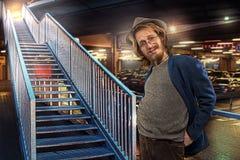 Tillfredsställd rolig man vid trappan, underjordisk parkeringsplatsbakgrund Arkivbild