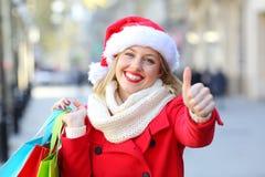 Tillfredsställd shoppare med tummar upp på jul arkivfoto