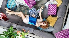 Tillfredsställd ung dam som ligger bland många shoppingpåsar royaltyfria bilder