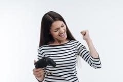 Tillfredsställd ung kvinna som lyfter hennes näve Royaltyfria Foton