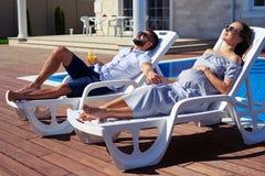 Tillfredsställda moderna par som får solbränna under solen royaltyfri bild