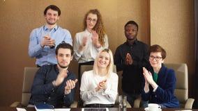 Tillfredsställda olika kontorsarbetare som applåderar händer efter affärsseminarium