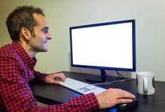 Tillfredsställda säkra manstirranden på kontorsdatoren på träsvart skrivbordmodell Prucken röd skjorta, LCD-skärm, tangentbord, m royaltyfria foton