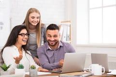 Tillfredsställt affärslag som tillsammans arbetar på bärbara datorn arkivfoto