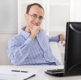 Tillfredsställt affärsmansammanträde i hans kontor med datoren Arkivfoto