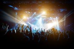 Tillfredsställt folk på konserten, kulört ljus från etappen royaltyfri foto