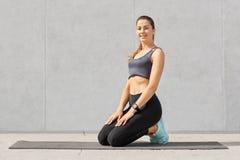 Tillfredsställt le kvinnan som är i godaändring, når att ha gjort, knastrar på matt kondition, står på knä, iklädd sportswear, ha royaltyfri foto