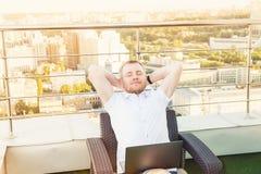 Tillfredsställt med gjort arbete Gladlynta innehavhänder för ung man bak huvudet och hållaögon stängt, medan sitta på terrassen m royaltyfri bild