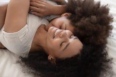 Tillgiven afrikansk mamma- och barndotter som omfamnar att ligga på säng royaltyfri foto