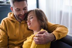 Tillgiven make och fru som kopplar av i vardagsrum fotografering för bildbyråer