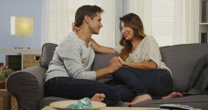 Tillgivna blandade par som talar på soffan royaltyfria bilder