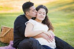Tillgivna gravida latinamerikanska par som utomhus kysser i parkera Royaltyfri Bild