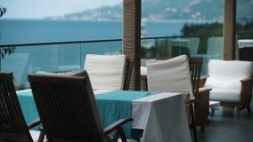 Tillgripa äta middag område på balkongen över träd med scenisk sikt på havet stock video