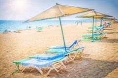 Tillgripa den tropiska stranden med paraplyer och solsängar Royaltyfri Bild