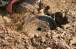 Tilling the Soil. Soil tilling device in motion, preparing a garden area for planting Stock Photography