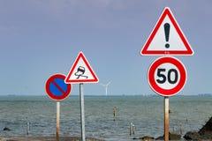 Tillsammans av vägmärken bredvid havet Arkivbild