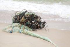 Tilltrasslade fisknät på stranden Arkivbild