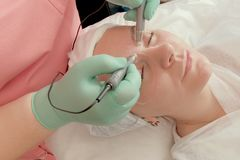 Tillvägagångssättet av elektrisk stimulans mot blåmärken under ögonen Ögonomsorg i skönhetsalongen Rengörande Cosmetology för fra arkivbilder