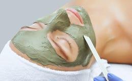 Tillvägagångssättet för att applicera en maskering från lera till framsidan av en härlig kvinna Royaltyfri Bild
