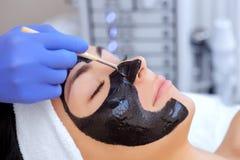 Tillvägagångssättet för att applicera en svart maskering till framsidan av en härlig kvinna royaltyfri foto
