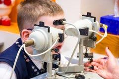 Tillvägagångssättet för undersöknings- och maskinvarubehandlingögonen av ett barn Barnet sitter framme av ophthalmological behand arkivfoto