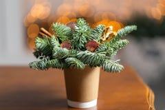 Tillverka pappers- kaffekoppar på en trätabell Begreppet av julkaffe med garneringgranträdet på bakgrunden Royaltyfri Foto
