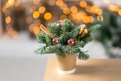 Tillverka pappers- kaffekoppar på en trätabell Begreppet av julkaffe med garneringgranträdet på bakgrunden Arkivfoto