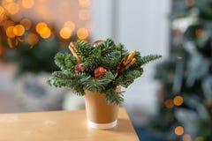 Tillverka pappers- kaffekoppar på en trätabell Begreppet av julkaffe med garneringgranträdet på bakgrunden Arkivbilder