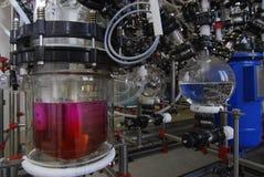 Tillverkning av mediciner på en drogfabrik karmosinröd flytande i en flaska Arkivfoto
