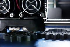 Tillverkning för FDM 3D-printer sporrar kugghjul från silver-grå färger glödtråd på bandet för det blåa trycket royaltyfria foton