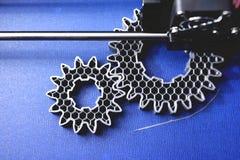Tillverkning för FDM 3D-printer sporrar kugghjul från silver-grå färger glödtråd på bandet för det blåa trycket - bästa sikt Royaltyfri Fotografi