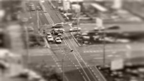 Tilt–shift cars in traffic, seen from above. Tilt–shift cars on the road, intersection, aerial view stock footage